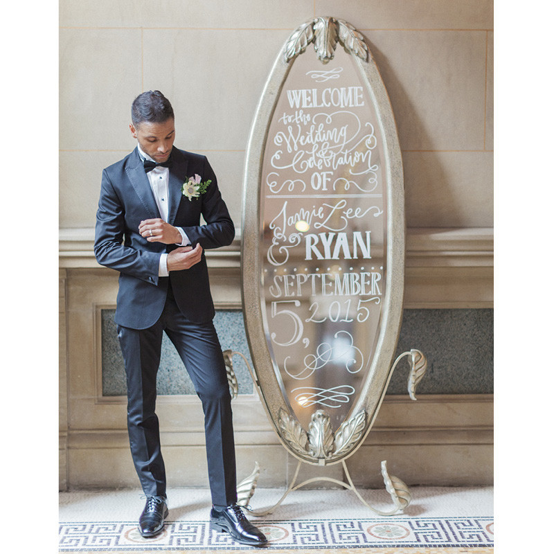 A groom standing next to a mirror.