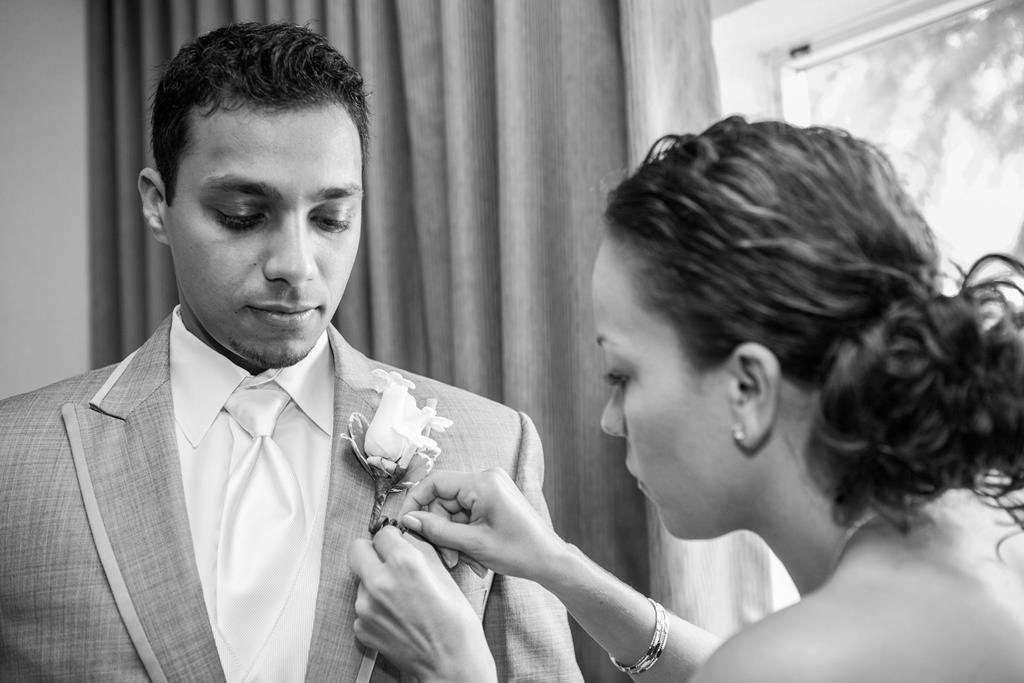 The Maitre D' helping a groom with his boutonniere.