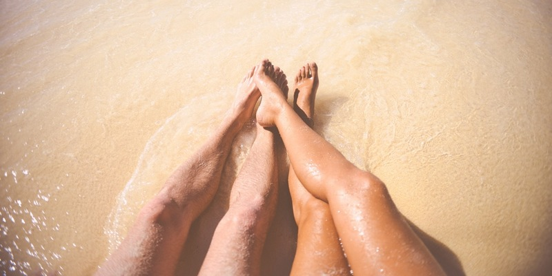 The legs of a couple lying on the sand.