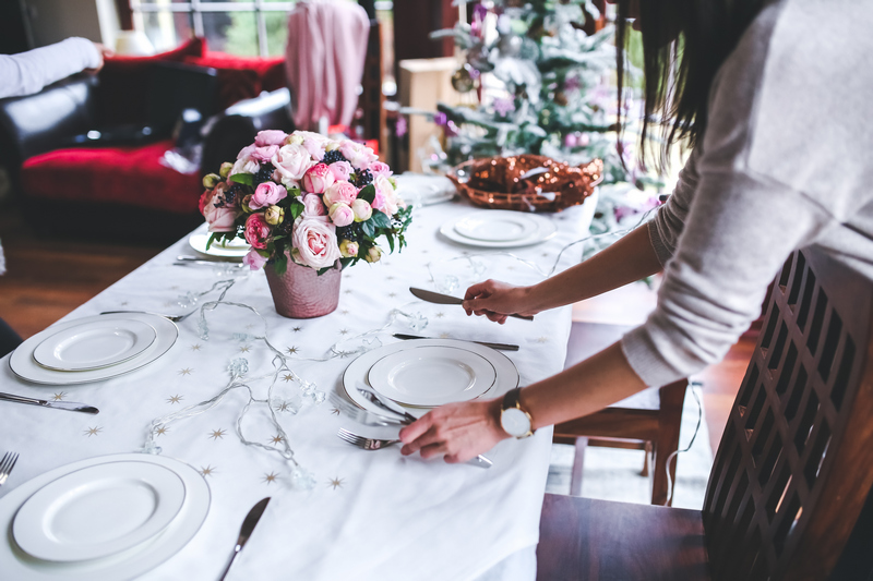 A wman setting up a wedding table with flowers.
